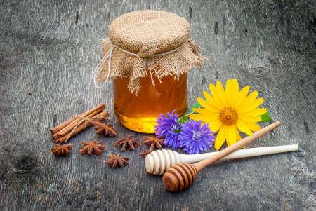 Honey in jar with honey spoon on vintage wooden background