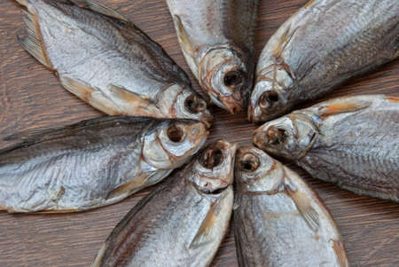 some dried fish on a dark wooden background / Stock Photo
