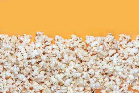 Tasty salted popcorn on yellow background