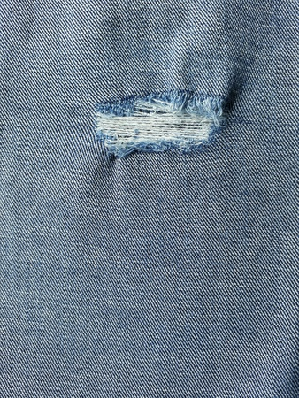 Close up of the inside of denimjeans with hole and threads texture. Stock Photo