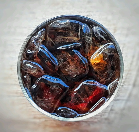 Top view of a glass of cola with ice on white background, selective focus.