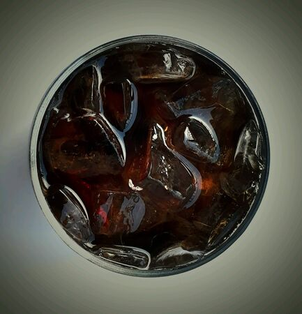 Top view of a glass of cola with ice background, selective focus.