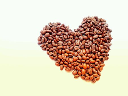 Closeup top view pile of coffee beans in heart shape background, selective focus.