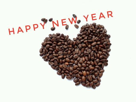 Closeup top view of pile of coffee beans in heart shape with HAPPY NEW YEAR banner on white background