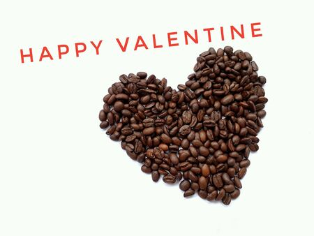 Closeup top view of pile of coffee beans in heart shape with HAPPY VALENTINE banner on white background