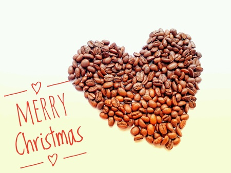 Closeup top view pile of coffee beans in heart shape with MERRY Christmas banner on white background