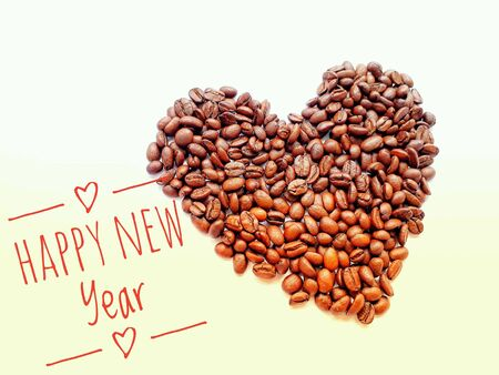 Closeup top view pile of coffee beans in heart shape with HAPPY NEW Year banner on white background Stock Photo