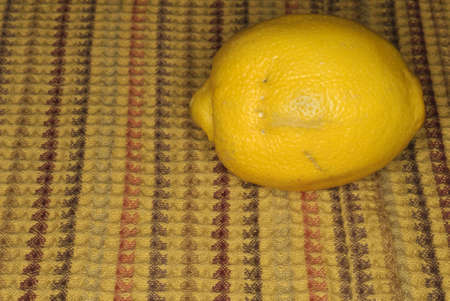A lemon with a fork mark in it sits on a dish towel.