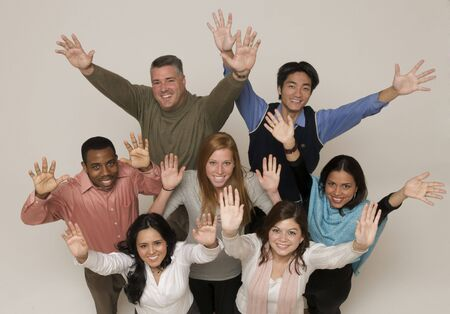 ethnically diverse: ethnically diverse group of university age people hands in the air on white studio background Stock Photo