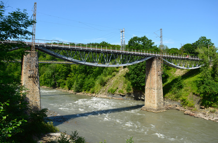 old railway bridge built over the mountain river Stock Photo