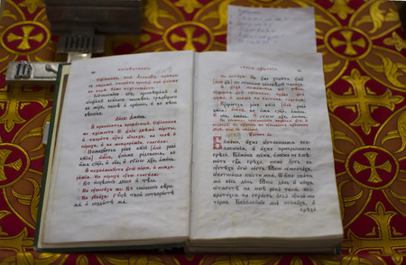 slavonic: open old Bible written in Old Church Slavonic language , church on red cloth with crosses Stock Photo
