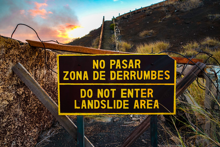 Do not enter, landslide area written in Spanish and English. Sing in the Masaya Volcano national park in Nicaragua, central America.