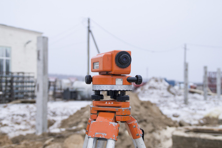 tripod mounted: The measuring device theodolite at construction site