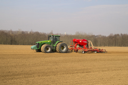 pneumatic tyres: modern power tractors on the field planting produces pneumatic seed drill