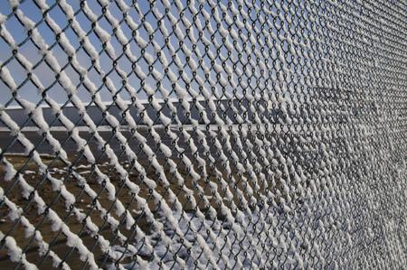 penetración: valla de malla de alambre cubierto de nieve Foto de archivo