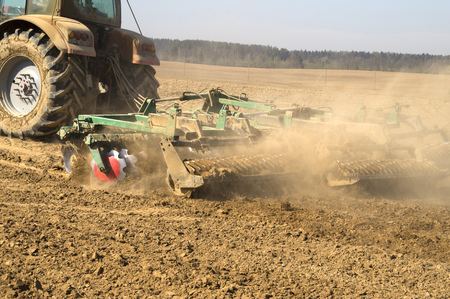harrow: Modern power tractor pulling a harrow on the field in autumn