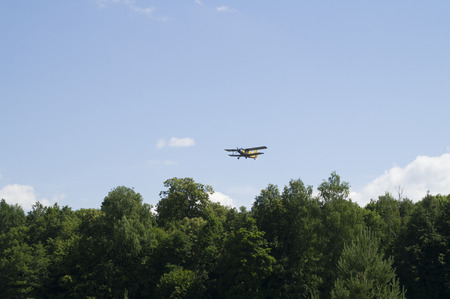 biplane: Light aircraft biplane flying over the forest Stock Photo