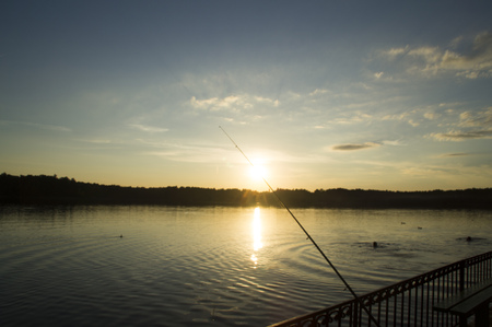 pier: Sunset over the lake and fishing rod on the pier