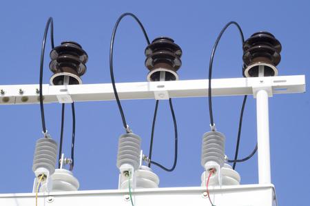 porcelain insulators of high-voltage substation on blue sky