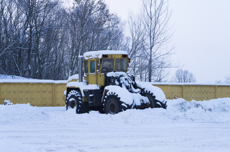 discolored: old tractor under the snow
