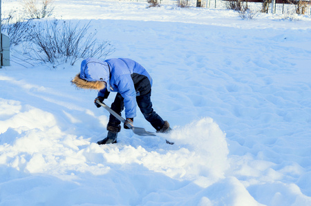 little boy digs snow shovel