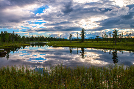Beautiful reflection of the sky in the middle of the swamp. Amazing shapes in the clouds combined with the green summer tundra.