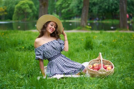 a girl in a hat and a blue dress is sitting on the grass in the Park.girl with a basket of apples near the lilac