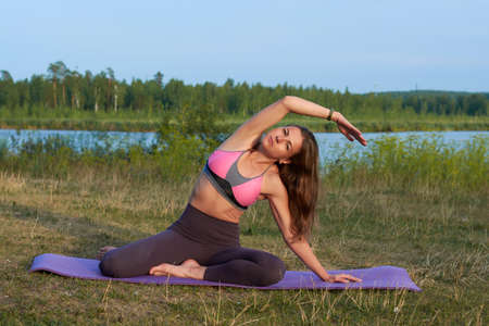 a young woman does yoga in nature.yoga poses and practice