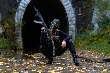 a woman in a black suit and gas mask with a machine gun in her hands.