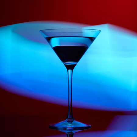Martini glass on a red background with blue lights Foto de archivo