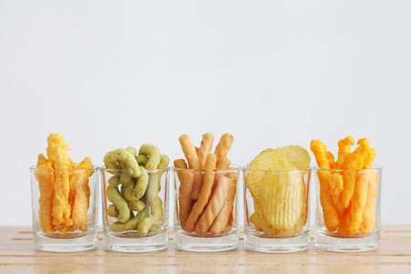 Snacks in the glasses on the wooden table with white background and copy space