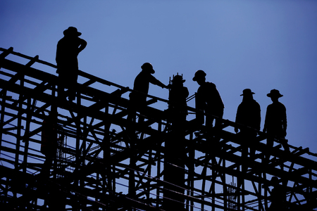 Construction worker is working on steel roof , silhouette , blue sky