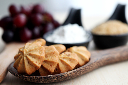 Grape cookies on woodenspoon with sugar , grape , flour and woodentable background
