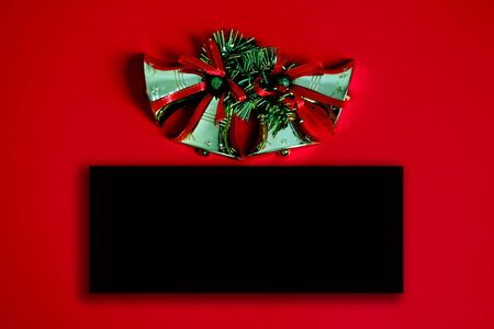 Christmas bell and blackboard with copy space on red background