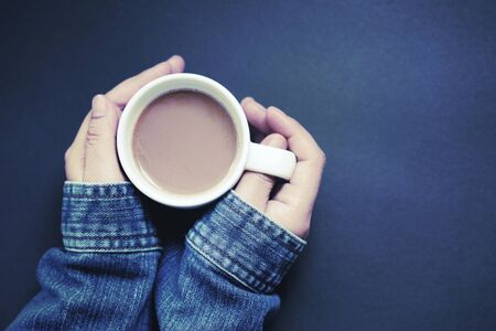 Hand holding a cup of hot coffee with dark blue background 写真素材