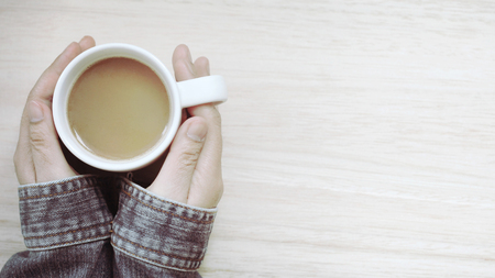 Hand holding a cup of hot coffee on wooden background