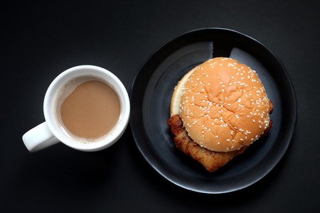 Chicken Burger and hot coffee on black background , top view , close up