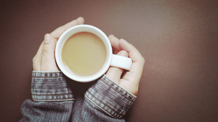 Hand holding a cup of hot coffee with retro background
