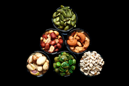 Mix Nut in the glass on gray background , close up , peanut; Peas; Sunflower seeds; Pumpkin seeds; cashew nuts; pistachios