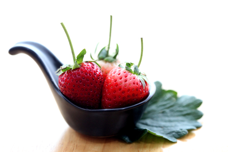 Fresh strawberries on black dish with white and wooden background