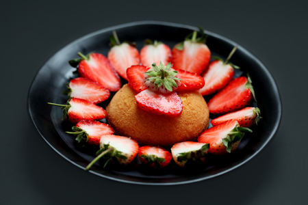 Fresh strawberries and cake on black dish with gray background
