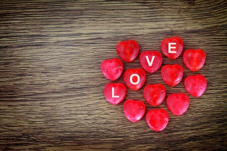 LOVE word on Red heart candy on wooden background with copy space
