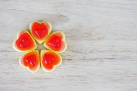 Red heart candy on wooden background with copy space