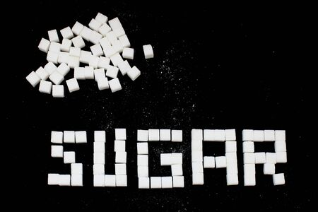 SUGAR word made from sugar cubes  on black background , close up , macro , with copy space 写真素材