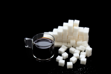 Sugar cubes with a cup of black coffee on black background , close up , macro , with copy space 写真素材