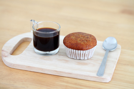 Banana cake with black coffee on wooden background