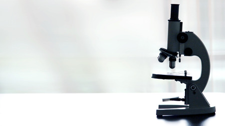 Microscope on white table on white background with copyspace , close up