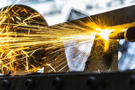 the worker cutting steel with an industrial cutter.