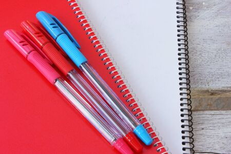 Notebook , Blue pen,Red pen,Pink pen ,Pens, blue pens, red pen color output on the notebook  photo