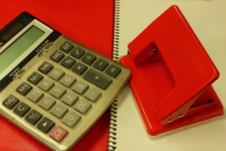 Red notebook and A paper punch and Calculator